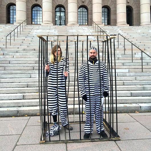 Vanginpukuihin pukeutuneet mielenosoittajat seisovat häkissä eduskuntatalon edessä ja puolustavat aseistakieltäytymisoikeutta