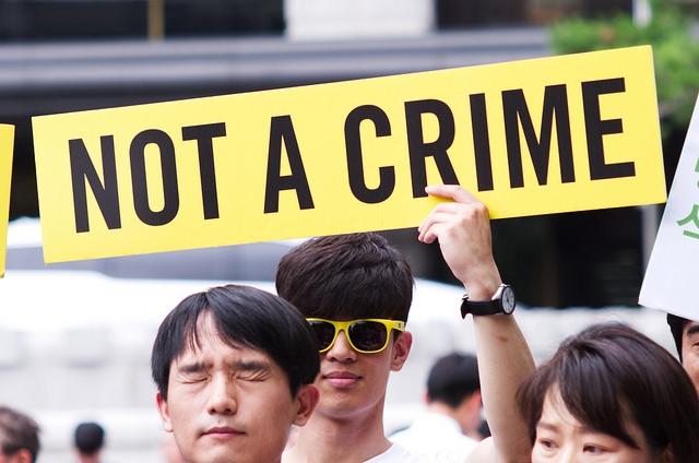 """Etelä-Koreassa osoitetaan mieltä aseistakieltäytymisoikeuden puolesta. Mielenosoittaja pitelee kylttiä jossa lukee: """"Not a Crime"""""""