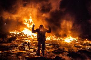 Mielenosoittaja tuulettaa heitettyään poliiseja poilttopullolla Maidanilla 25.1.2014.