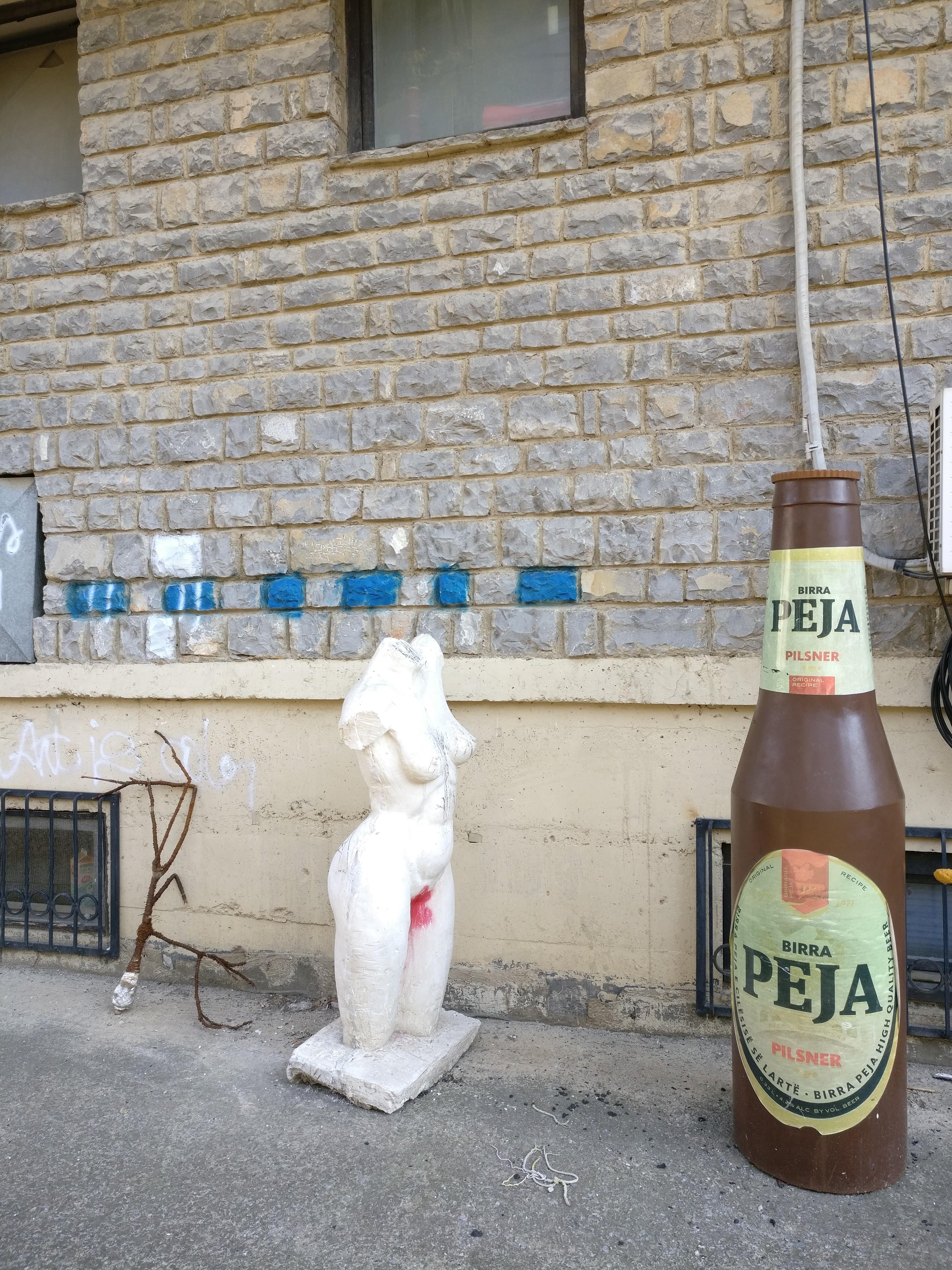 Patsas päättömästä naisesta ja oluesta. Kuva on otettu Pristinan ylipiston taideakatemian pihalta.